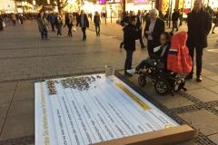 Gerhard Kastl im Gespräch mit Passanten an der Bodenzeitung Am Richard-Strauss-Brunnen in der Münchner Fußgängerzone